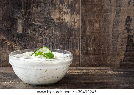 Tzatziki sauce in bowl on rustic wooden background