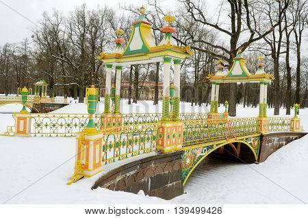 A white winter in the Park.With a snow background is highlighted with a yellow bridge.