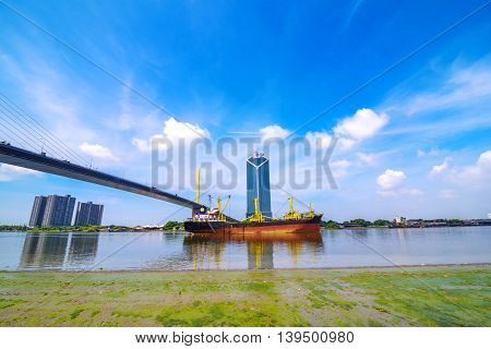 Huge Container Ship entering port of Bangkok, passing under the Bridge