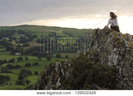 A Beautiful Woman Gazes Down at the Valley Floor from Atop a Windy Crag in Wales