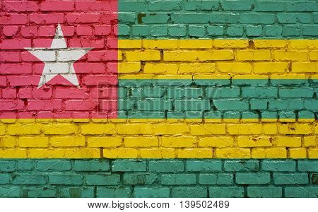 Flag of Togo painted on brick wall background texture