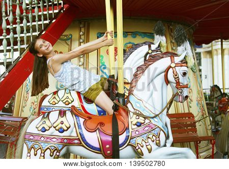 Young girl on a merry-go-round on top of horse