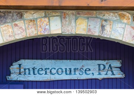 An Intercourse PA wood sign hanging in a brick archway.