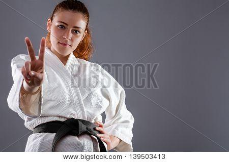 Woman Wearing Karate Kimono Showing Victory Sign