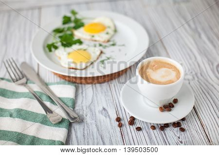 fried eggs coffe green fork knife wooden