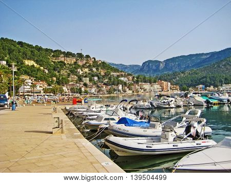 Port de Soller Majorca Spain - June 23 2008: View of harbor of Port de Soller - boats ships and yachts - promenade with palm trees in front.
