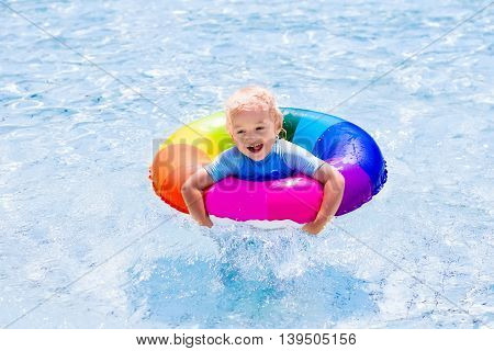 Happy little boy playing with colorful inflatable ring in outdoor swimming pool on hot summer day. Kids learn to swim. Children wearing sun protection rash guard relaxing in tropical resort