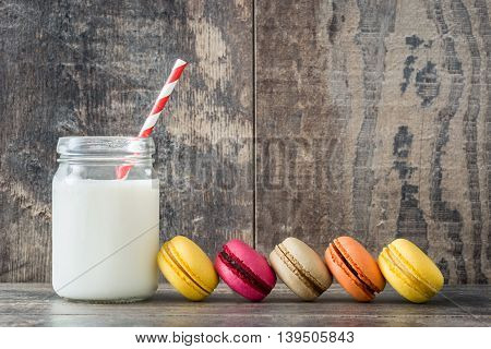 Sweet colored macaroons on rustic wooden background