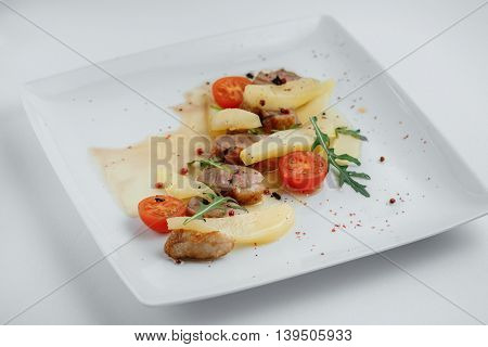 Pork With Pears, Tomatoes And Arugula On A White Background