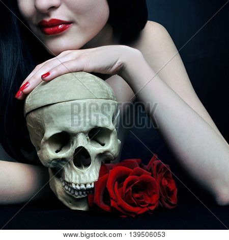 Brunette witch with skull and red roses