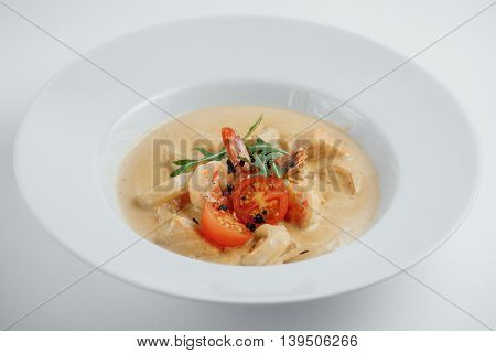 Seafood Soup With Tomatoes And Arugula In The White Plate