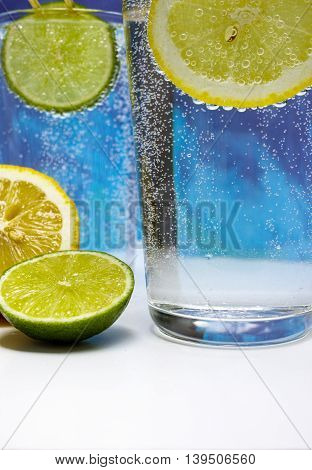 Glass with cold sparkling mineral water lime and lemon seltzer