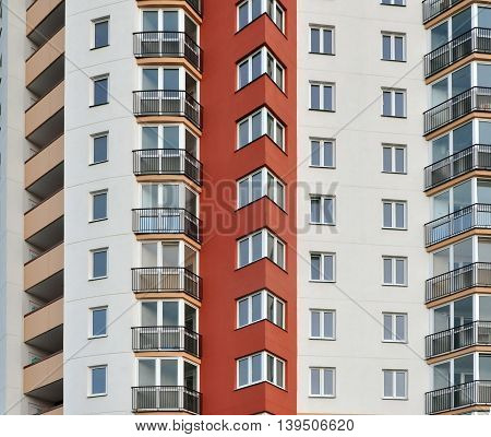 Front view of multistory modern residential building. White facade with red bay windows yellow balcony and glazing.