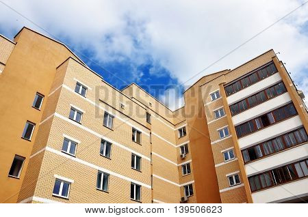 Look up at the modern multistory apartment building of beige brick against the cloudy sky.