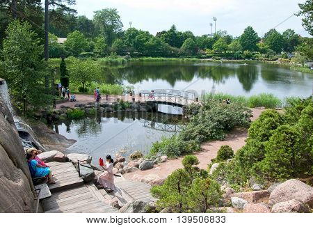 KOTKA, FINLAND - JUNE 26, 2016: People take pictures near waterfall in Sapokka Water Garden. It is most ecological center in the town.
