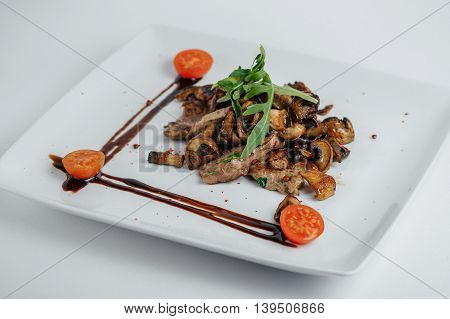Meat With Mushrooms, Tomatoes And Arugula On A White Plate
