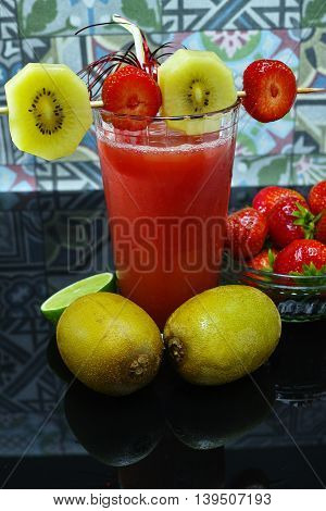 Fresh pressed strawberry and gold kiwi juice in a glass with fruits
