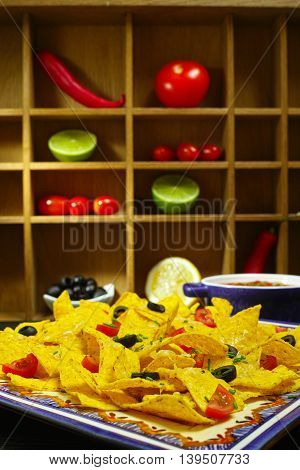 A plate of delicious tortilla nachos with melted cheese sauce chives onion black olives salsa on wooden rack background