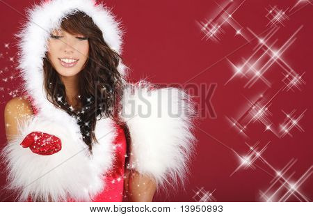 girl in santa cloth blowing snow from hands.