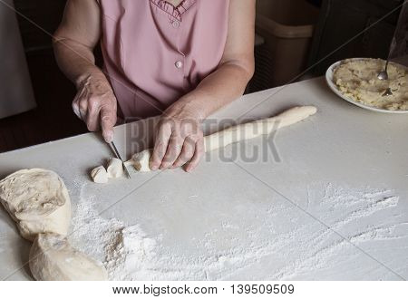 Hands Of An Old Woman Cut The Dough