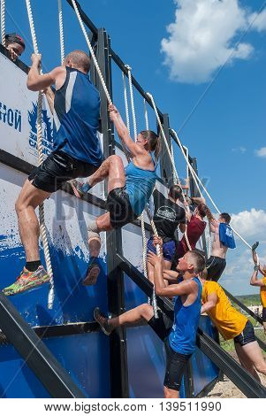 Tyumen, Russia - July 9, 2016: Steel Character extrim race on Voronino Hill. Vertical wall stage - high wooden fence with ropes. Athletes storm wall