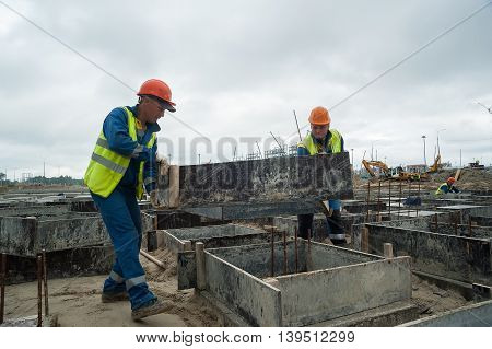 Tobolsk, Russia - July 15. 2016: Sibur company. Construction of plant on processing of hydrocarbonic raw materials. Workers do base for big oil tank