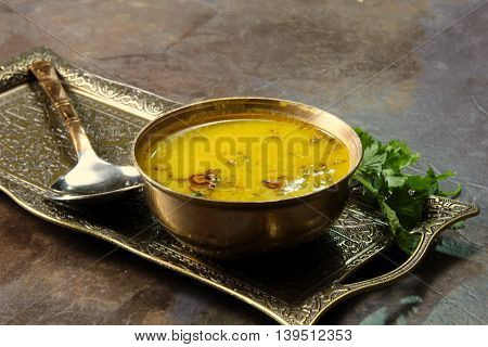 Yellow Lentil soup or Arhar Daal fry with the tadka of cumin seeds garlic and green chilies in a bowl on a tray with cilantro leaves on the side selective focus.