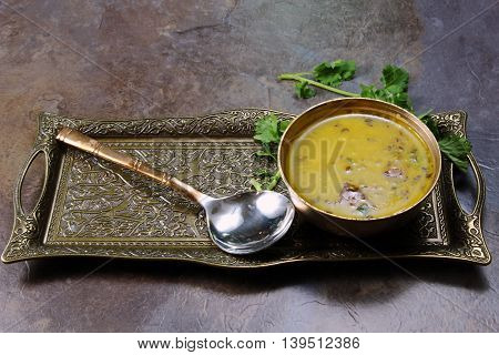 Yellow Lentil soup or Arhar Daal fry with the tadka of cumin seeds garlic and green chilies in a bowl on a tray with cilantro leaves on the side with copy space selective focus.