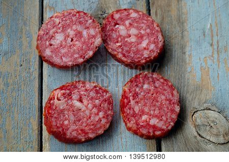 Slices of sausage on a rustic table. Rustic salami. salami slices.