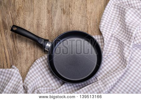 An empty pan on a wooden table and tablecloth background