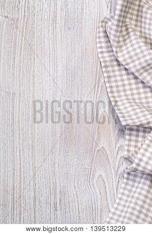 the checkered tablecloth on wooden table background