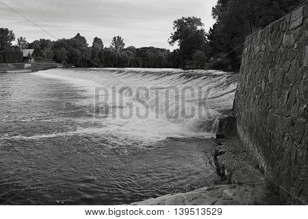black and white photography of water weir on the river Ohre in the village Hostenice in Ceske stredohori region in Czech republic