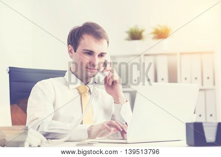 Businessman speaking on phone and making notes on computer office at background. Concept of work. film effect