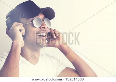 Portrait of happy african american guy in cap and glasses listening to music with headphones on light background. Film effect