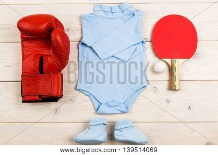 Future occupation concept. Top view of blue baby boy outfit surrounded with boxing glove and table tennis equipment on light wooden surface