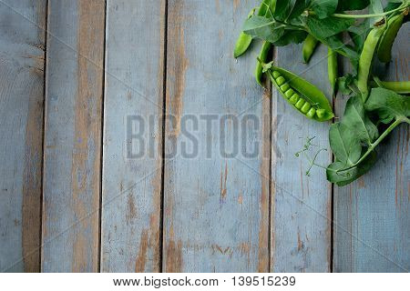 Green Peas In Pods Freshly Picked On Rustic Wooden Table