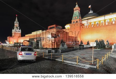 Red square by night in Moscow with a view of the Lenin mausoleum and the police car next to him