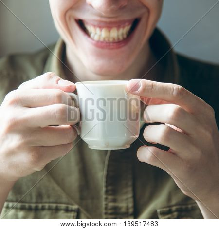 man smiles with cup of coffee. good morning concept