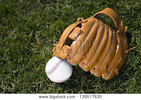 Baseball glove and ball on grass background.