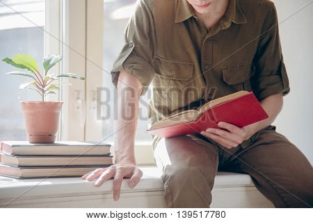 concentrated serious young man read book before university exam