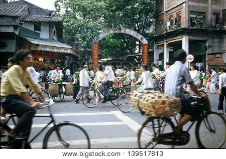 GUANGZHOU / CHINA - CIRCA 1987: People ride bicycles past the entrance to Guangzhou's Qingping Market.