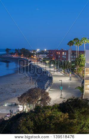 Concrete boardwalk lamps along the beach at dawn.