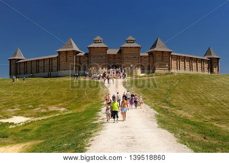 Eletz Russia - June 13 2015: Ethno folk festival at Kudykina Gora. Russian wooden castle replica and strolling people horizontal