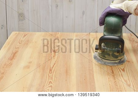 Electric Sander. Carpenter sanding a wood with sander