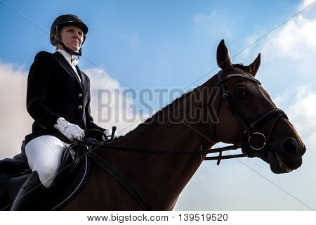 Serious Jockey Woman Sitting On A Horse.
