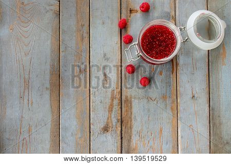 Open a jar of raspberry jam on the wooden table. Background layout with free text space.