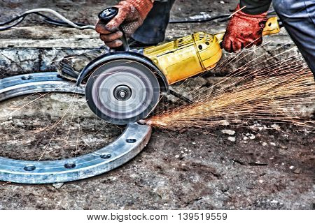 Worker with angle grinder and sparks in workshop taken closeup.Grunge toned image.