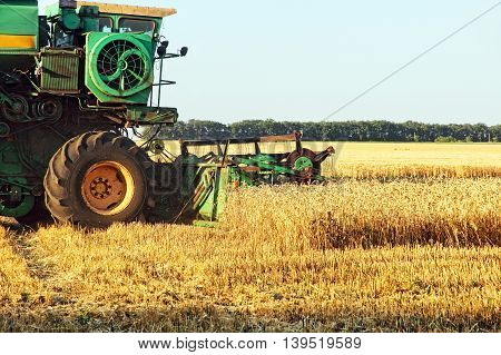 The photo of Combine harvester working in wheat field.