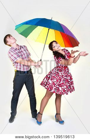 Young beautiful couple man and woman under colorful umbrella