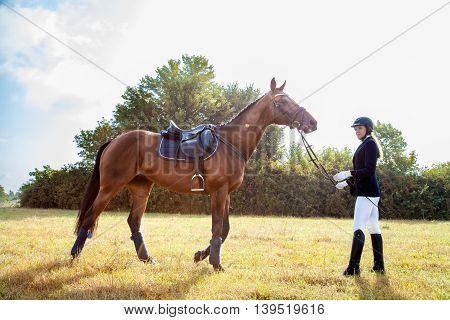 Beautiful Jockey Girl Stand Next To Her Horse.